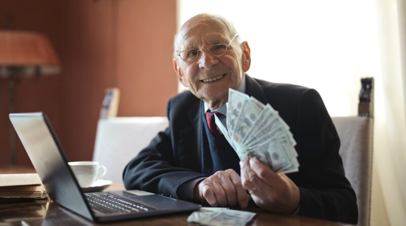 old man holding cash