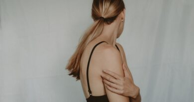 woman holding upper arm