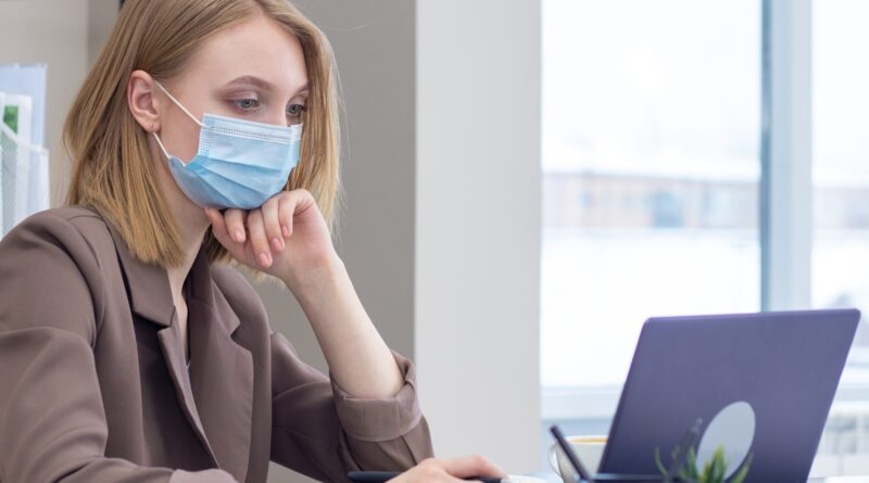 woman at desk wearing mask