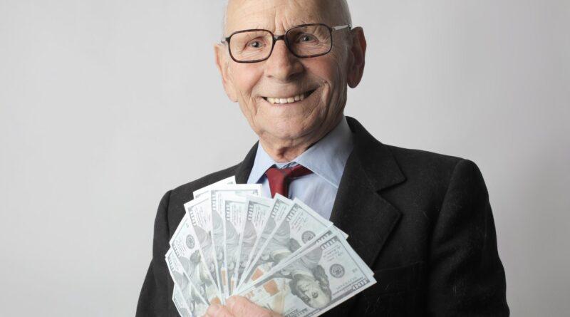 senior man holding cash
