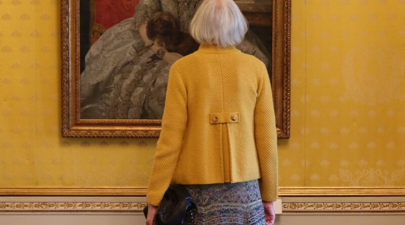older woman looking at painting