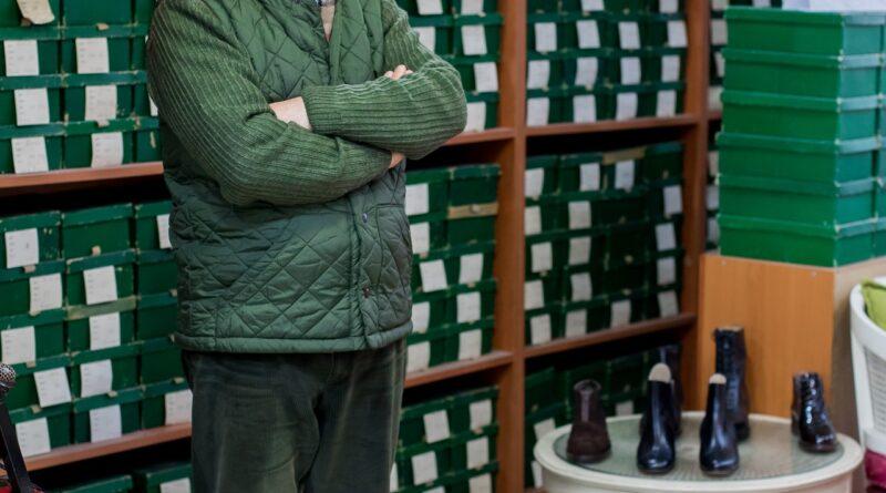 senior man working in shoe store